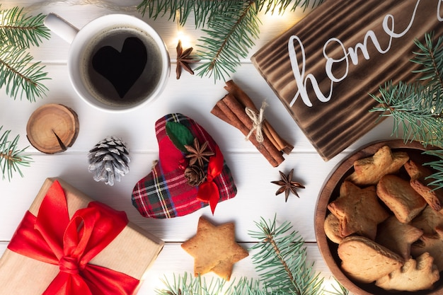 Home lettering burnt wood sign, gingerbread cookie, christmas tree branches, cup of coffee, gift, cinnamon sticks on white surface. flat lay