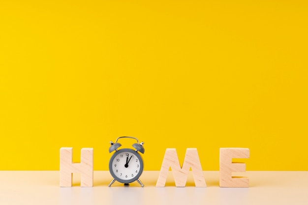 Home lettering with wooden letters and clock on yellow background