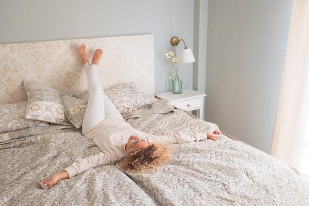 朝、自宅の寝室のベッドでくつろぐホーム ライフ スタイルの女性