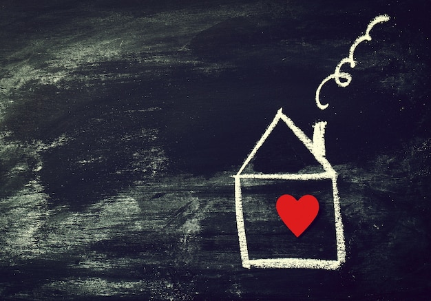 Home or love concept. painted house with red heart on a black ch