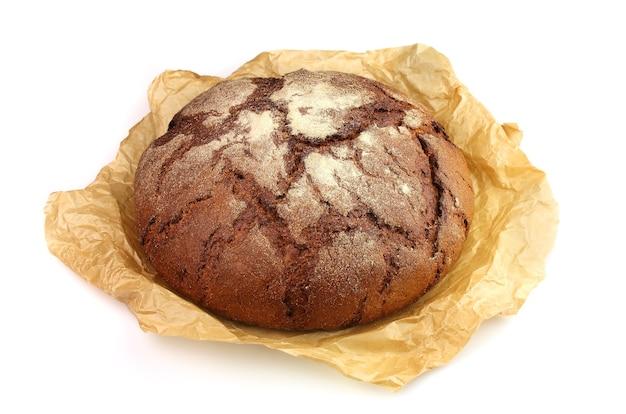 Домашний хлеб в пергаментной бумаге на белом фоне