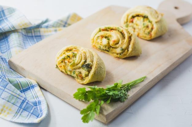 にんにく、パセリ、ピーマンをナプキンに入れ、木製のまな板を白くした自家製パン。