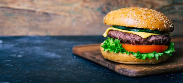 Home made burger (cheeseburger) with beef on a wooden background. classic home made burger.
