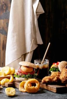 Домашние гамбургеры с луковыми кольцами и жареным картофелем, подаваемые с колой и хрустящим жареным куриным филе в панировке на темном фоне текстуры