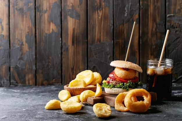 Home made burgers with onion rings and fried potatoes served with cola and crispy fried breaded chicken fillet on dark texture background