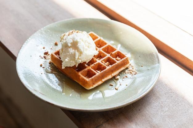 Домашняя классическая вафельная начинка с шариком ванильного мороженого. посыпать измельченным миндальным и кленовым сиропом. подается в керамической тарелке.