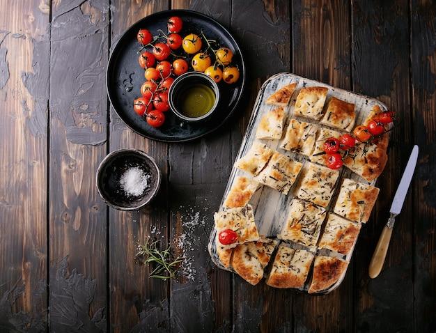 집에서 만든 focaccia 평평한 빵 조각으로 잘라 구운 토마토, 올리브 오일, 신선한 로즈마리, 빈티지 냅킨 및 나이프와 함께 나무 배경 위에 제공됩니다. 평면도