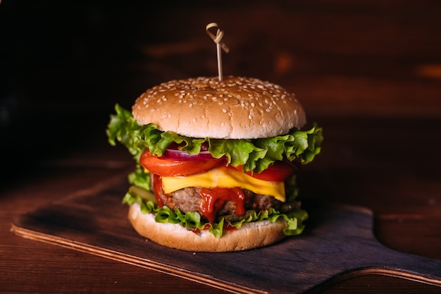Home made fresh tasty burger with lettuce and cheese on wooden rustic table. french fries, tomatoes and sauce. dark food background.