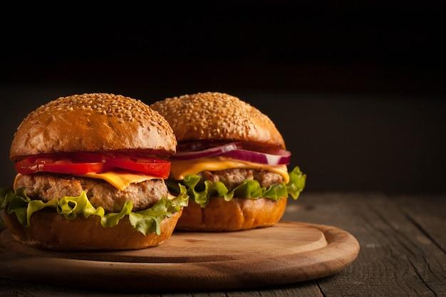自家製ハンバーグ、ビーフ、オニオン、トマト、レタス、チーズ。新鮮なハンバーガーは、ポテトフライ、ビール、チップと素朴な木製のテーブルにクローズアップ。チーズバーガー。