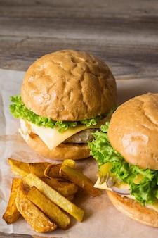 닭고기, 양파, 오이, 양상추, 치즈를 넣은 집에서 만든 햄버거는 감자 튀김이 있는 소박한 나무 테이블에 올려져 있습니다.