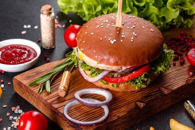 レタスとチーズの自家製ハンバーガー。木製のテーブルに自家製のおいしいハンバーガーのクローズアップ