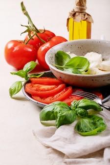 집에서 만든 건강한 식사 개념 : 체리 토마토, 모짜렐라 공, 향신료 및 신선한 바질. 흰색 질감 표면 위에 모짜렐라 샐러드입니다. 공간 복사