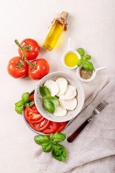 집에서 만든 건강한 식사 개념 : 체리 토마토, 모짜렐라 공, 향신료, 올리브 오일 및 신선한 바질. 흰색 질감 표면 위에 모짜렐라 샐러드입니다. 평면도, 평면 위치