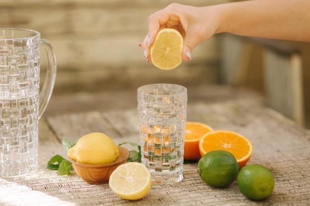 집에서 만든 건강한 비타민 강화 물 여성이 물에 레몬 주스를 짜냅니다