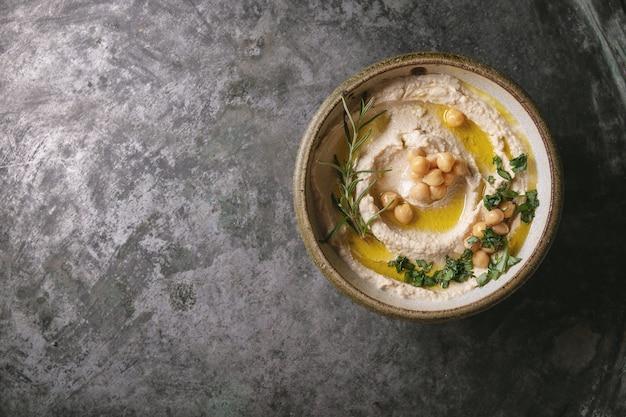 소박한 금속 배경 위에 삶은 병아리 콩, 허브, 올리브 오일로 장식 된 집에서 만든 후 무스 그릇. 평면도.