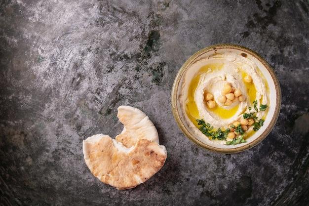 소박한 금속 배경 위에 삶은 병아리 콩, 허브, 피타 및 올리브 오일로 장식 된 집에서 만든 후 무스 그릇. 평면도.