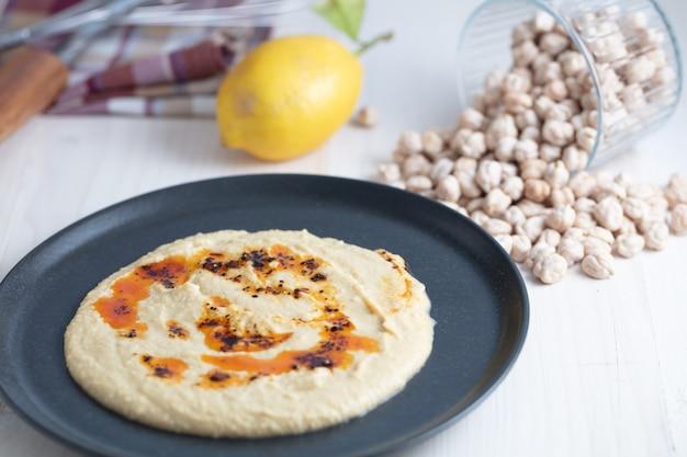 소박한 흰색 배경 위에 삶은 병아리콩, 레몬, 올리브 오일로 장식된 홈메이드 후무스 그릇.
