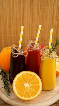 Домашний лимонад в бутылочках. разноцветные соки и фрукты на деревянных фоне. вертикальное фото