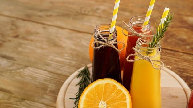 小さなボトルに入った自家製レモネード。木製の背景に色とりどりのジュースや果物