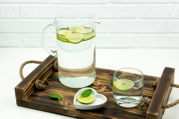 A home made lemonade made of lime stands in a glass and jug on a wooden tray