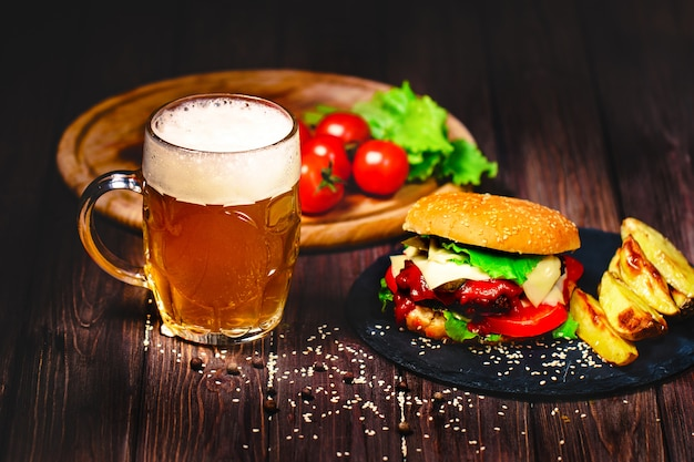 Home made mouth-watering, delicious beef burger with lettuce and potato, glass of beer served on stone cutting board. dark