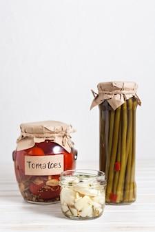 明るい背景のガラスの瓶に自家製の漬物トマト、ニンニク、アスパラガス。コピースペース。発酵野菜ヘルシーで美味しいです。