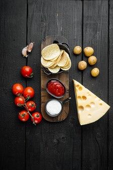 チーズとタマネギをセットした自家製ポテトチップス、黒い木製のテーブル、上面図フラットレイ