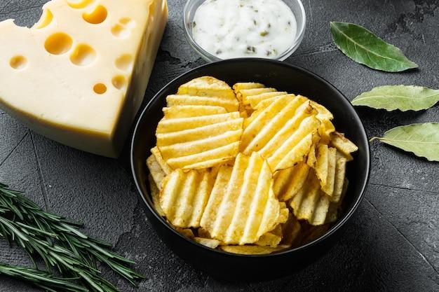 회색 돌 배경에 디핑 소스와 함께 치즈와 양파로 만든 집에서 만든 감자 칩