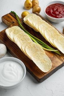 흰색 돌 표면에 소스 토마토 딥 사워 크림을 곁들인 집에서 만든 감자 칩 세트