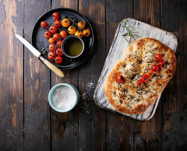 집에서 만든 로즈마리 focaccia 평평한 빵은 나무 배경 위에 구운 토마토, 올리브 오일, 신선한 로즈마리, 바다 소금 및 칼과 함께 제공됩니다. 평면도