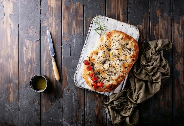 집에서 만든 로즈마리 focaccia 평평한 빵은 구운 토마토, 올리브 오일, 신선한 로즈마리, 빈티지 냅킨 및 나이프와 함께 나무 배경 위에 제공됩니다. 평면도