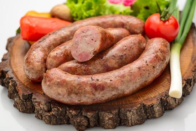 Домашняя колбаса с овощами на деревянной доске