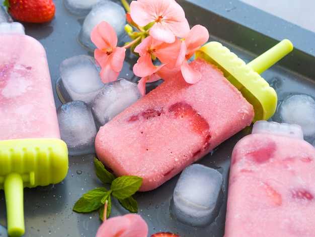 Home made strawberry ice cream popsicles on metall tray with ice cubes