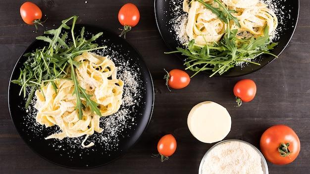 木製のテーブルにモッツァレラチーズとチェリートマトを添えた黒いプレートの自家製タリアテッレパスタ
