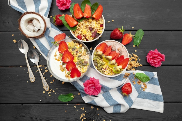 Home-made yoghurt with granola, fruit and coconut top view on wooden background