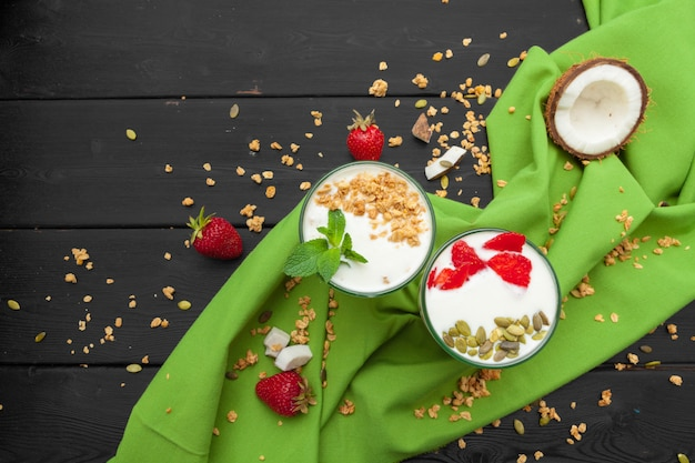 Home-made yoghurt with granola, fruit and coconut top view on wooden