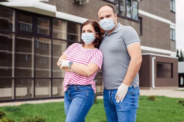 Домашний режим и самоизоляция во время карантина и эпидемии. семья мужчина и женщина в медицинских масках и перчатках на улице города.