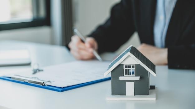 Домашняя модель подписывает контракт после того, как агент по недвижимости объясняет покупателю коммерческий контракт