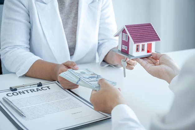 Home model in hands, the real estate agent explains the business contract, rent, purchase, mortgage, a loan, or home insurance to the business buyer.