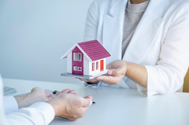 Home model in hands, the real estate agent gives a house model to the business buyer.