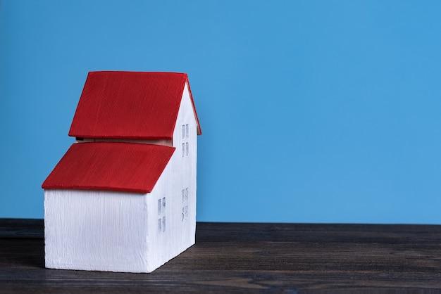 Домашняя модель на синем фоне. концепция кредита вид сбоку