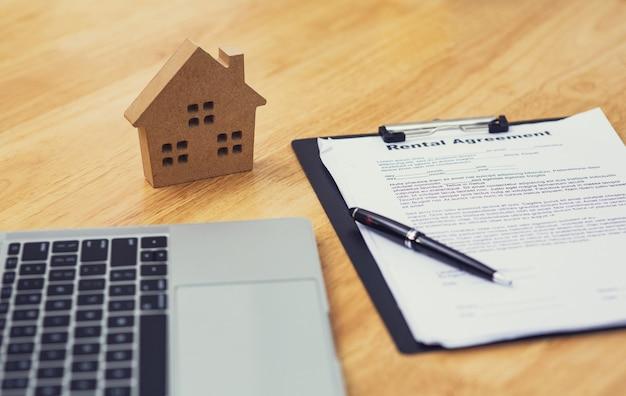 Домашняя модель, положенная рядом с документом об аренде или договоре аренды и ноутбуком для бизнеса в сфере недвижимости