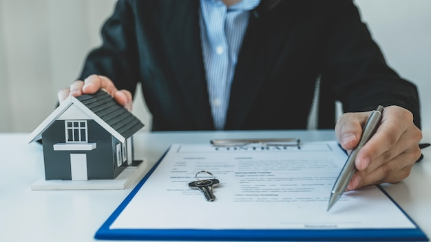 Home model. real estate agent hand holding pen and explain the business contract, rent, buy, mortgage, loan, or home insurance.