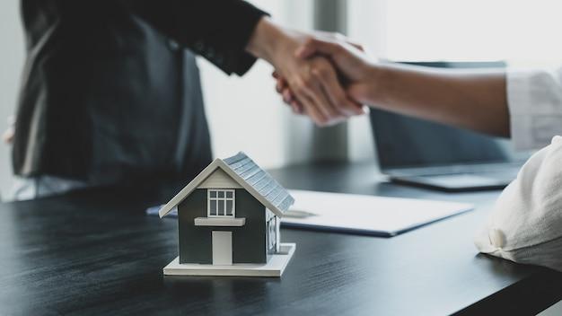 Домашняя модель. агенты по недвижимости и покупатели обмениваются рукопожатием после подписания делового контракта, аренды, покупки, ипотеки, кредита или страхования жилья.