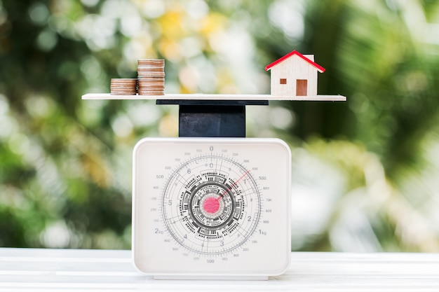 Home money coins on balance weighing scales on wood green background.