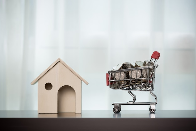 Home and money in the shopping basket on wooden table transparent curtain background.