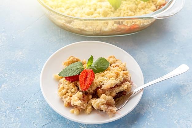 Домашний ñ ooking. крошка из ревеня или клубники, хрустящая корочка без глютена в форме для выпечки. летний десерт на тарелке на синем фоне.