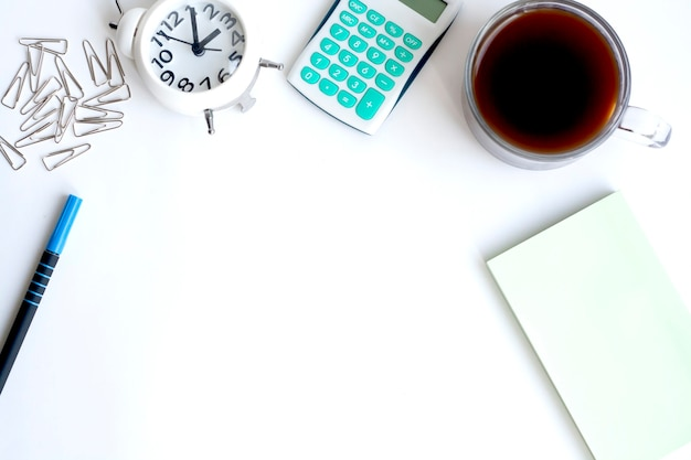 Home office, clock, calculator, note paper, paper clips, pen and a cup of coffee on white background, copy space