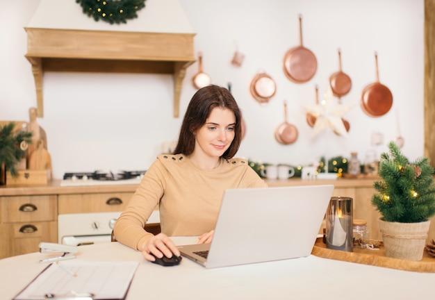 ホームオフィスのコンセプト。冬の明るいキッチンで自宅のラップトップに取り組んでいる若いフリーランスの女性。