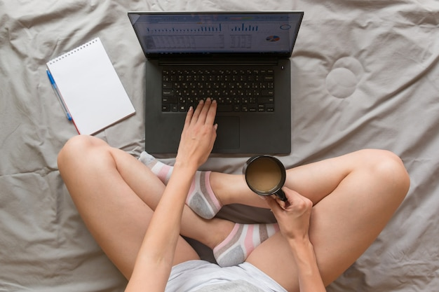 Home office concept: girl working with laptop in bed at home